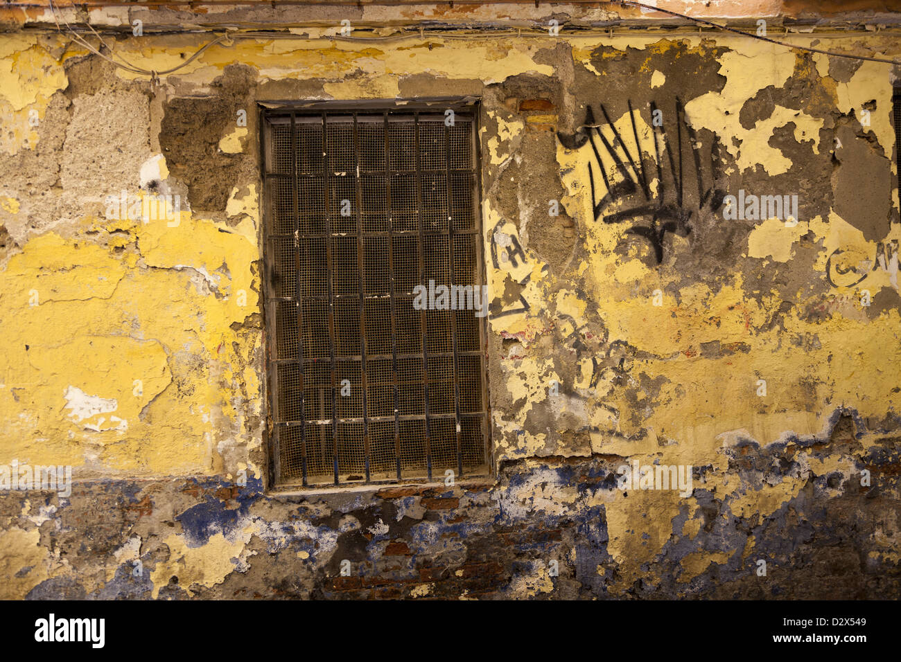 Old peeling wall and window with bars and wire mesh grill