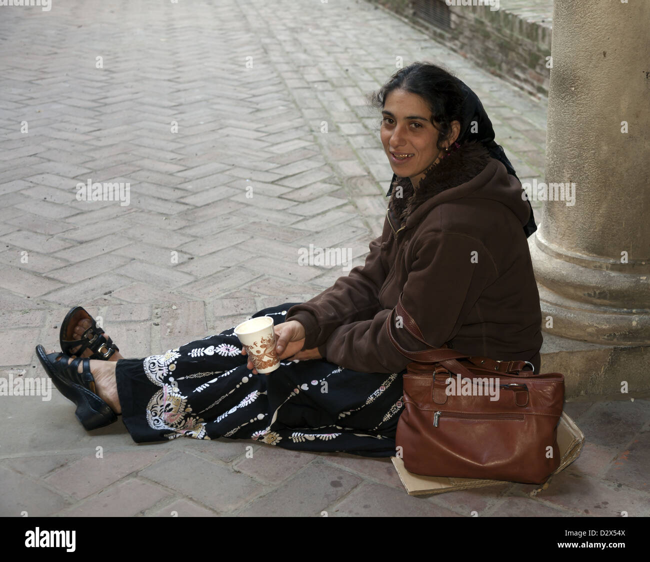 Female beggar with gold capped teeth sitting on cardboard holding paper cup to collect money Malaga Spain Stock Photo
