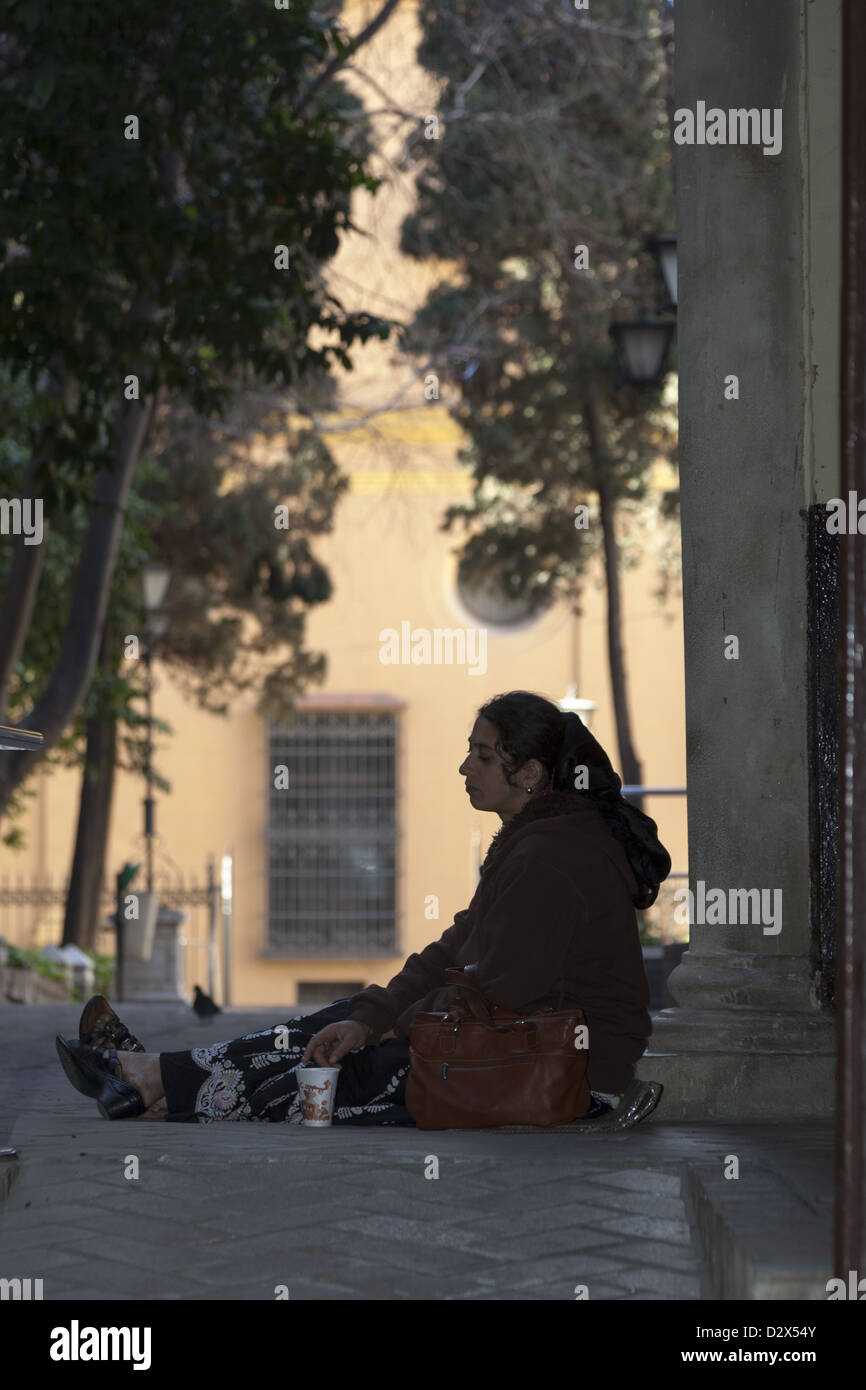 Female beggar sitting on cardboard holding paper cup to collect money in passageway of Malaga Spain - Stock Image