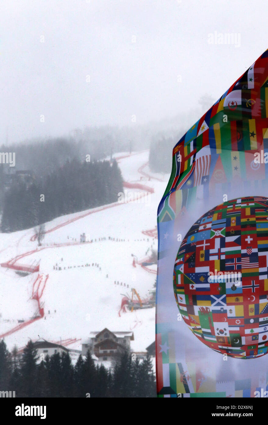 A flag that shows flags of different countries all over the world waves in front of the downhill in Schladming, - Stock Image
