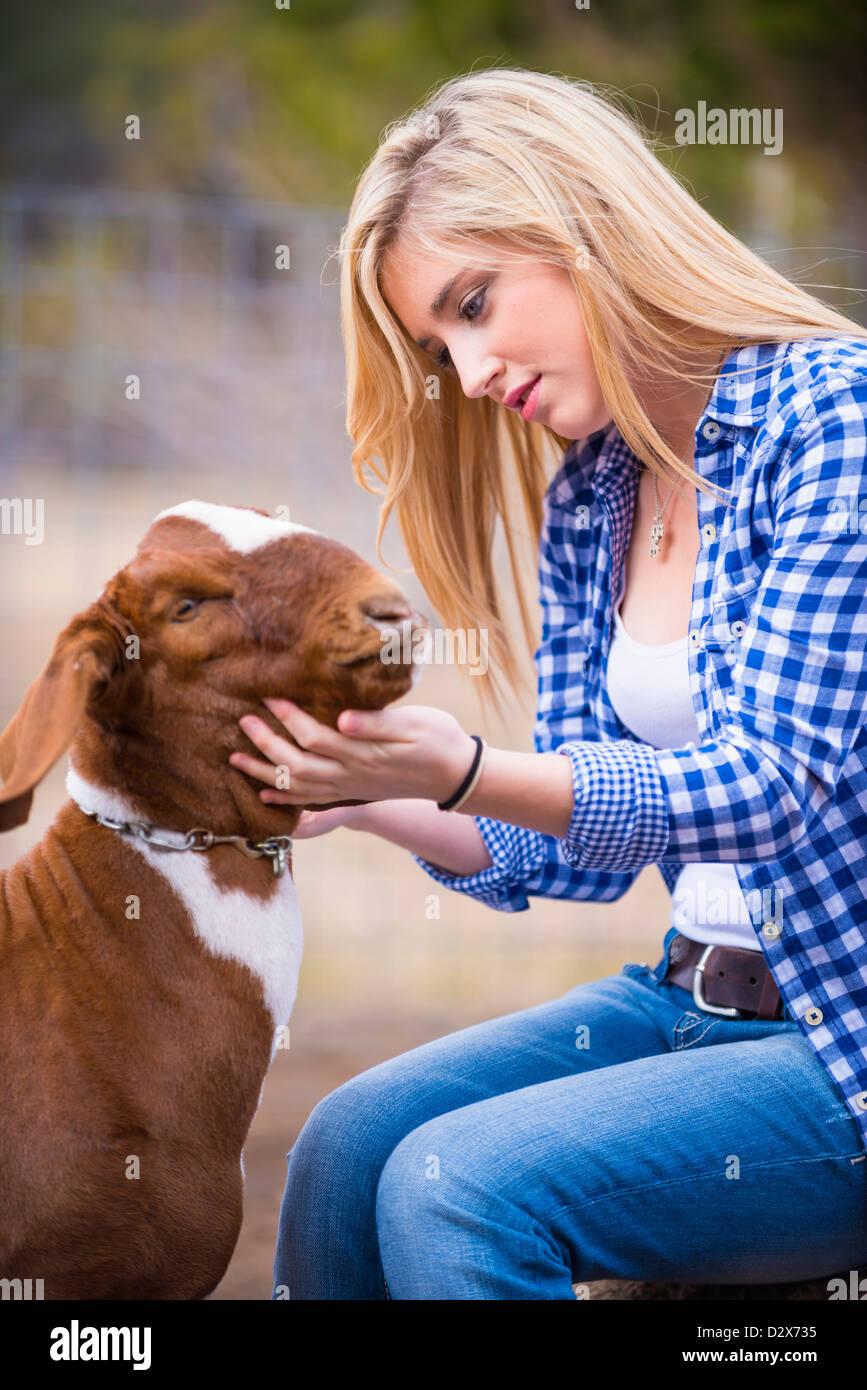 Female teenager petting goat - Stock Image