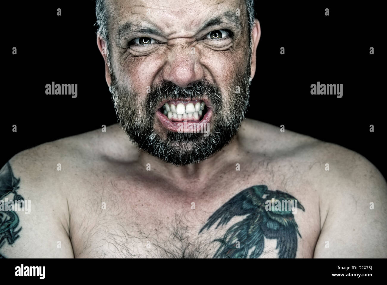 An image of an angry man with a beard - Stock Image