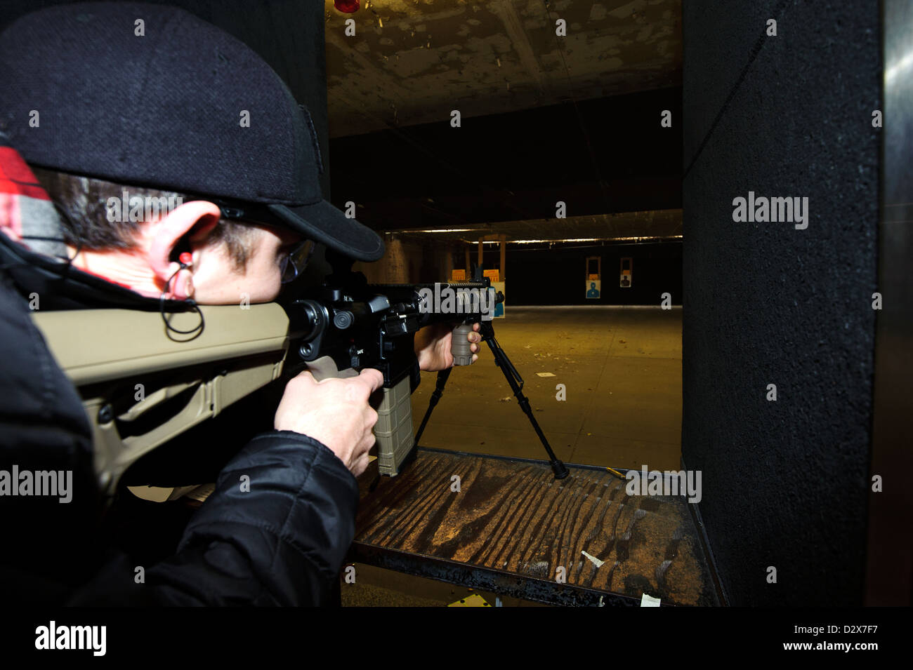 Target shooting with an AR-style target rifle at an indoor range Stock Photo