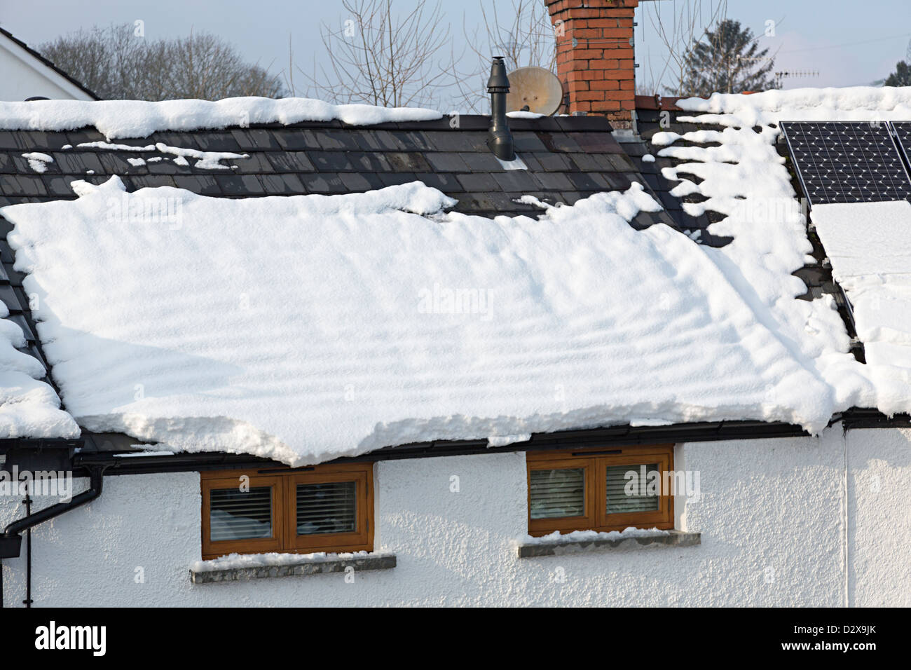 Snow sliding off tiled roof and putting weight onto gutters of house, Llanfoist, Wales, UK - Stock Image