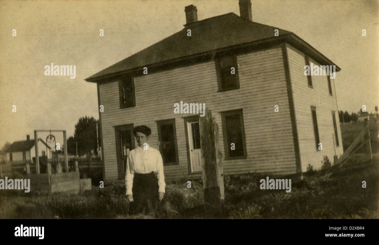 Circa 1910s photograph, a woman in front of her prairie farmhouse. - Stock Image