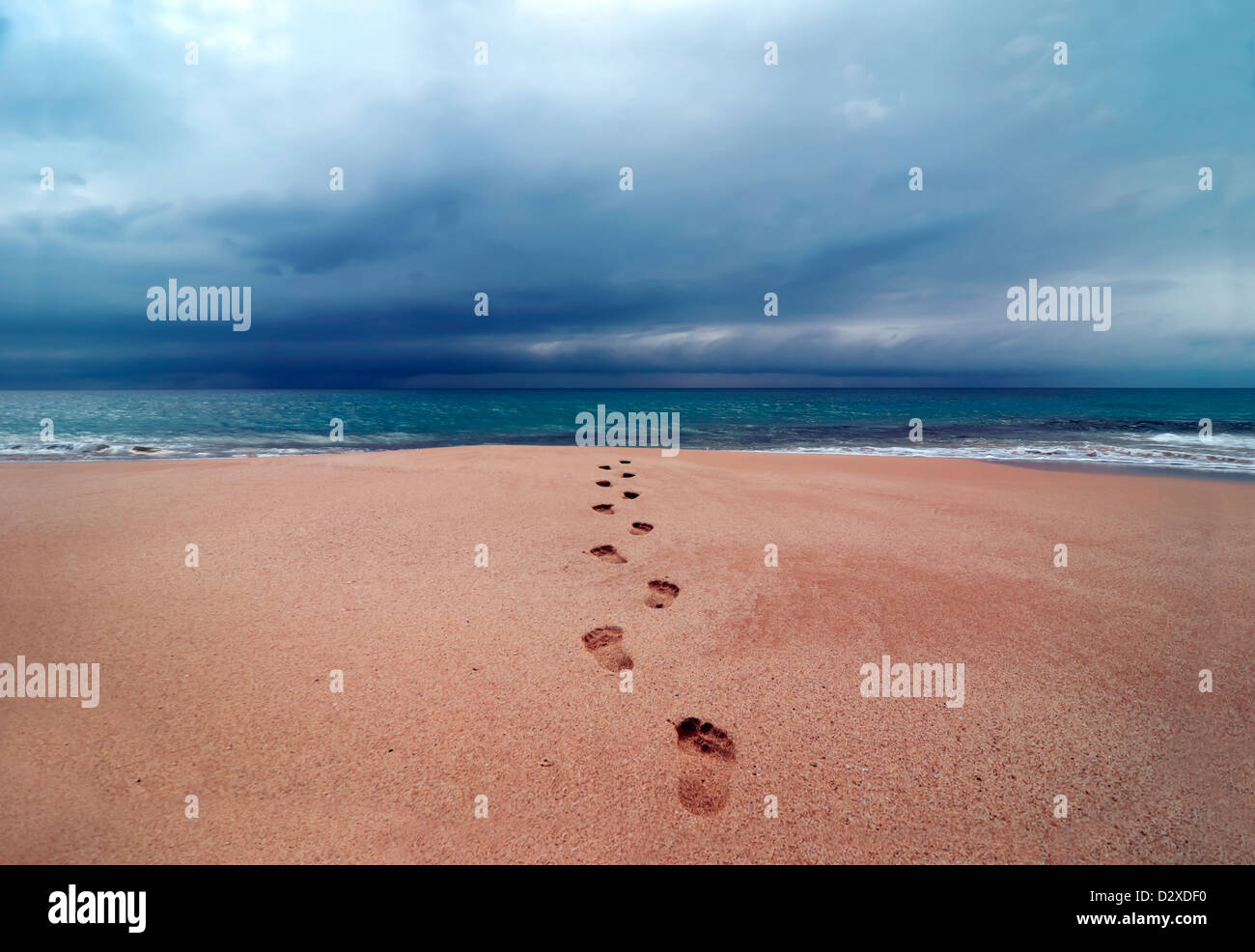 Big storm with clouds over footprints in soft sand leading into the ocean, Papohaku Beach, Molokai, Hawaii, USA, - Stock Image