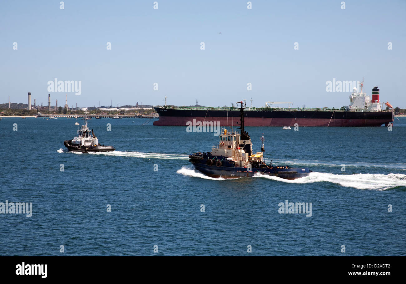 Harbour tugs passing in front of the liquid bulk carrier 'British Beech' departing from Kurnell Botany Bay - Stock Image