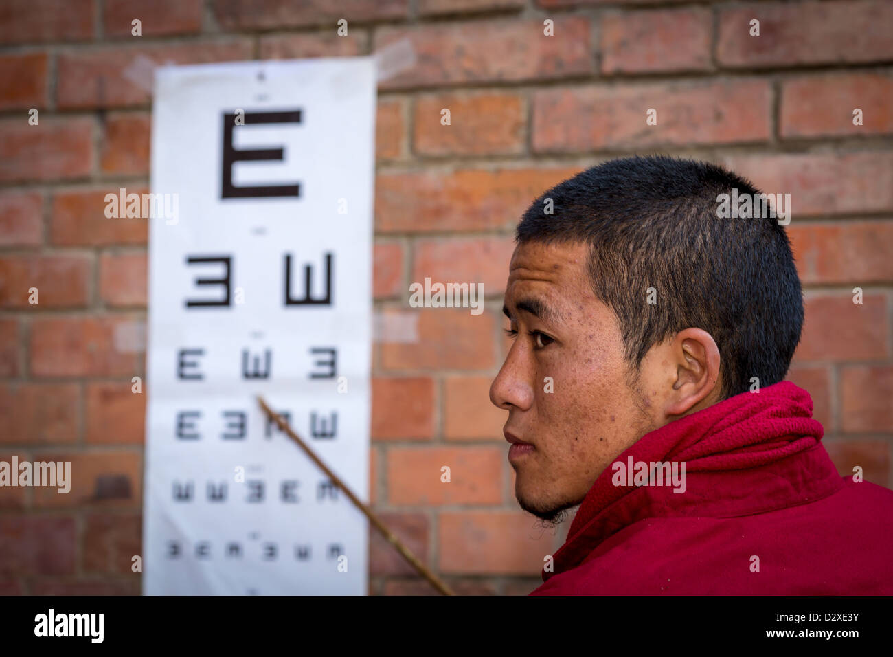A monk from Amitabha monastery caring out a charity vision test for poor villagers. Amitabha Monastery, Nepal, Asia - Stock Image
