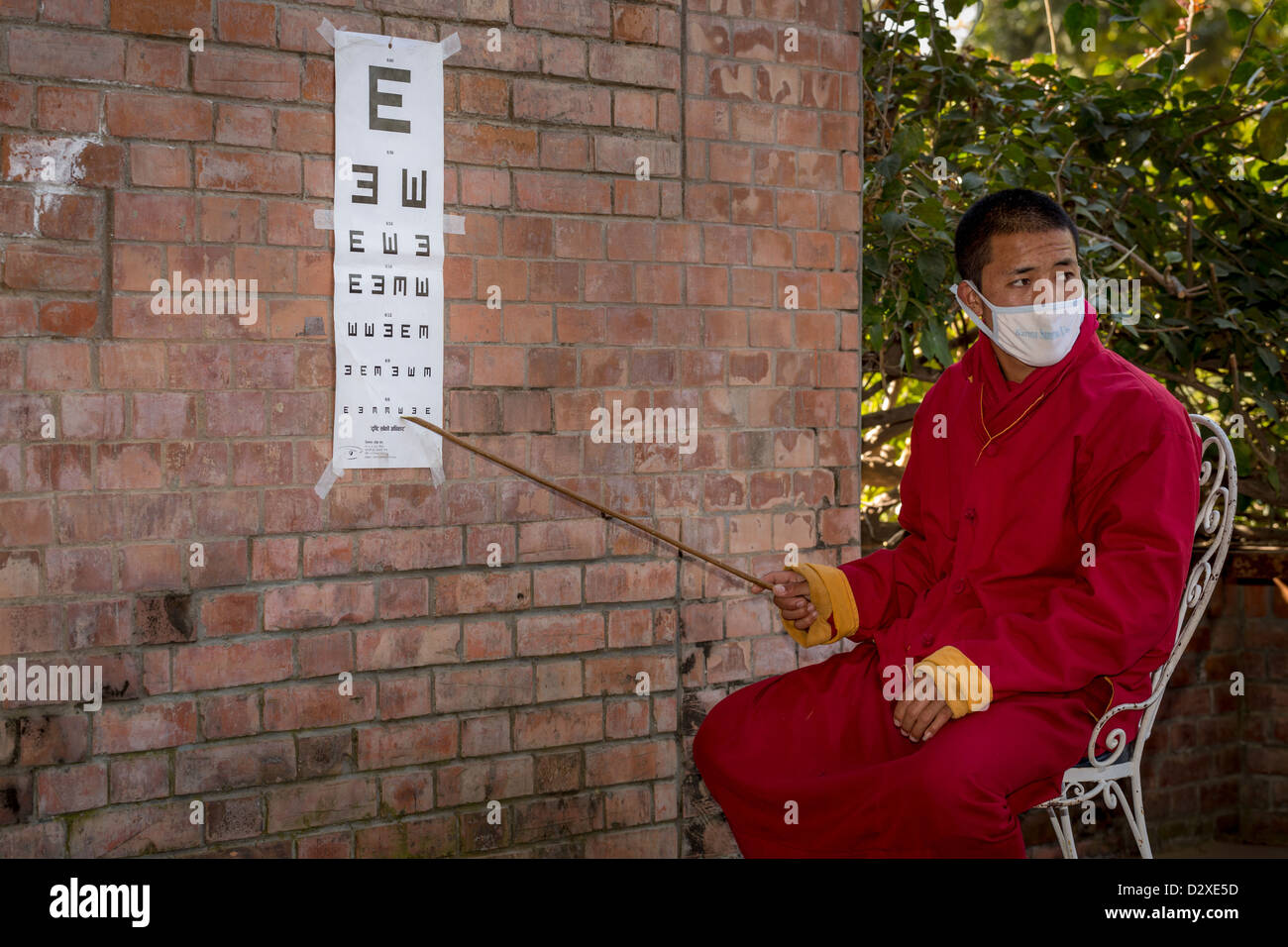 A monk from the Amitabha Monastery caring out a charity vision test for poor villagers. Amitabha Monastery, Nepal, - Stock Image