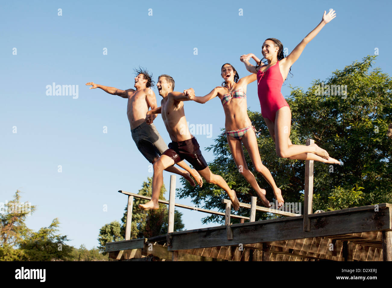 Friends jumping off dock Stock Photo
