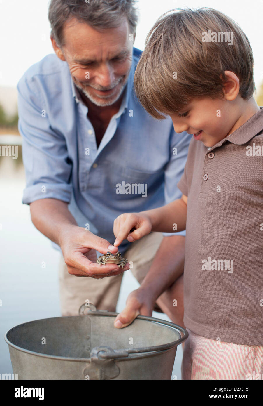 Grandfather and grandson with frog and bucket - Stock Image