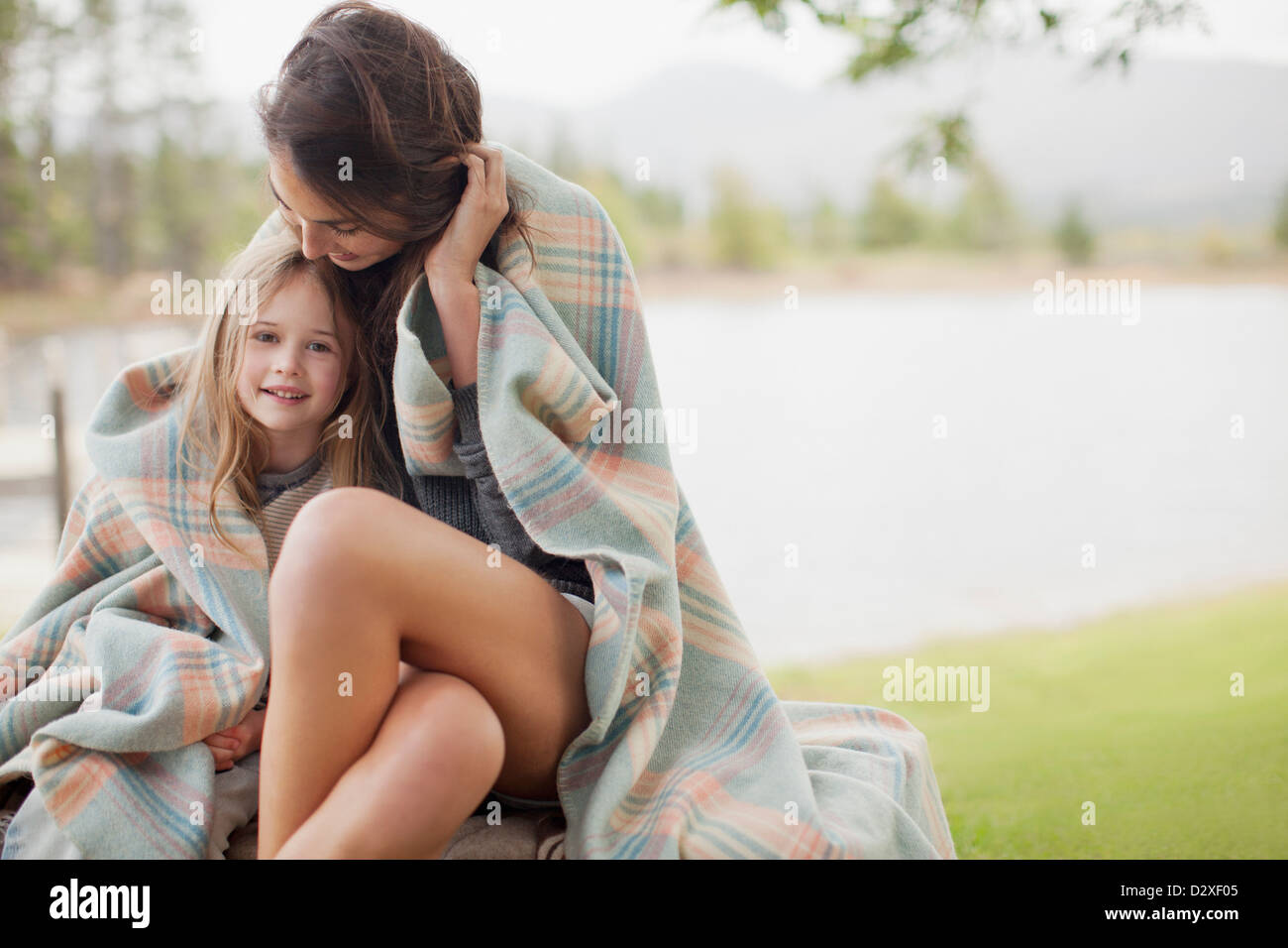 Portrait of smiling daughter wrapped in blanket with mother at lakeside - Stock Image