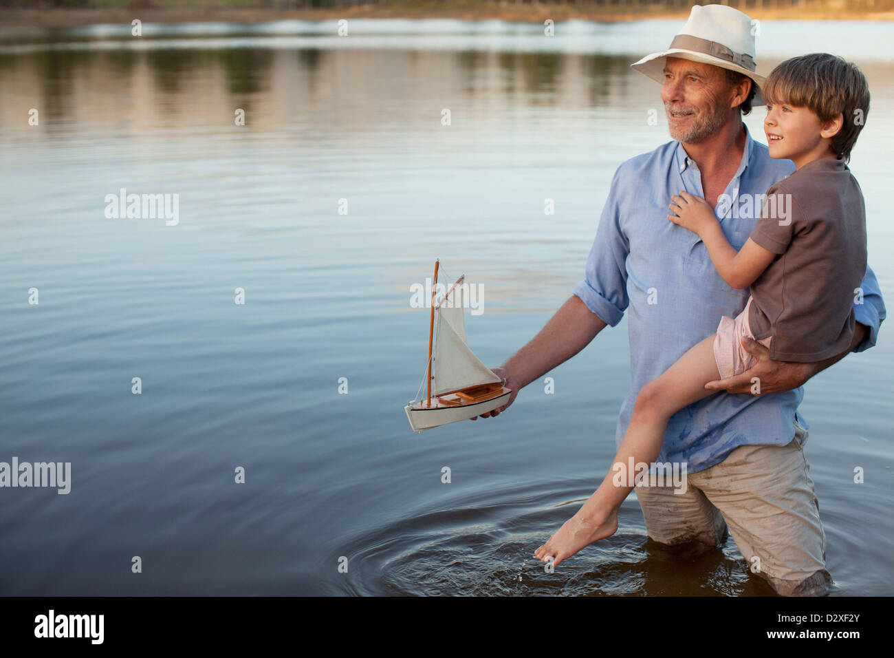 Grandfather and grandson with toy sailboat in lake Stock Photo