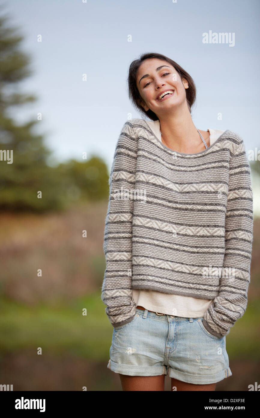 Portrait of smiling woman with hands in short pockets Stock Photo