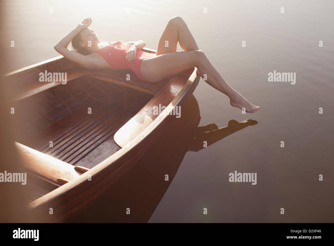 Serene woman sunbathing in boat on lake Stock Photo