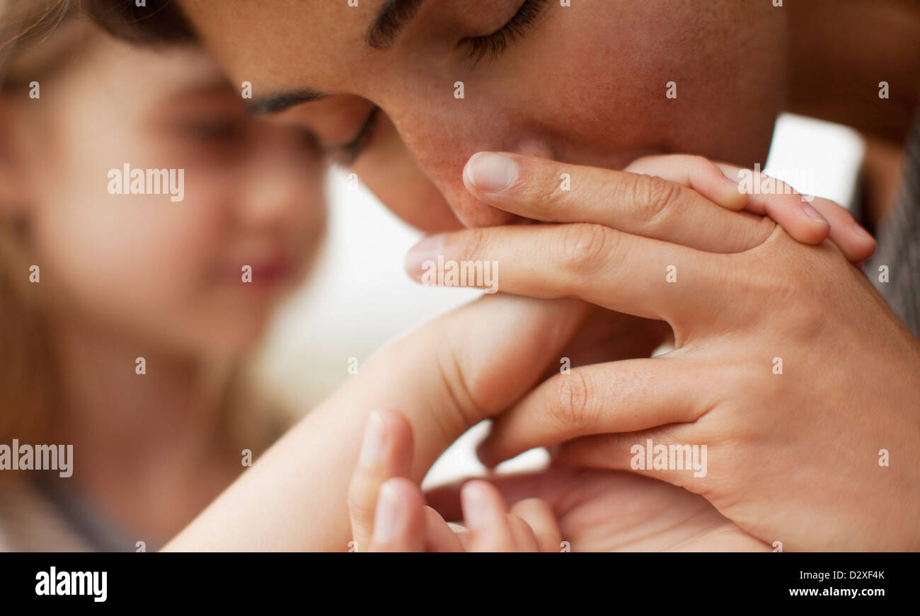 Close up of mother kissing daughter's hand - Stock Image