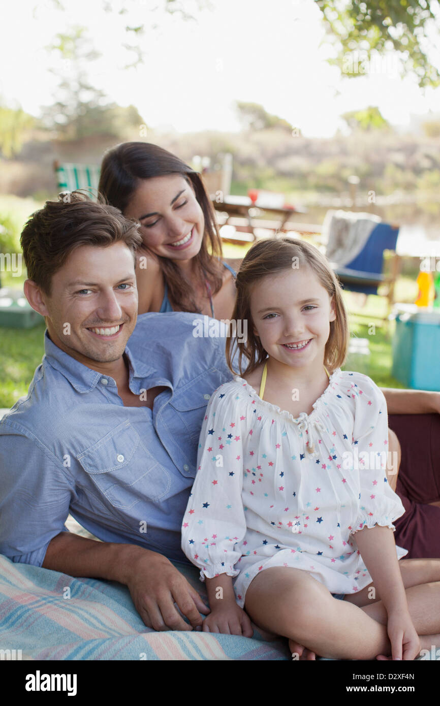 Portrait of smiling family picnicking at lakeside - Stock Image