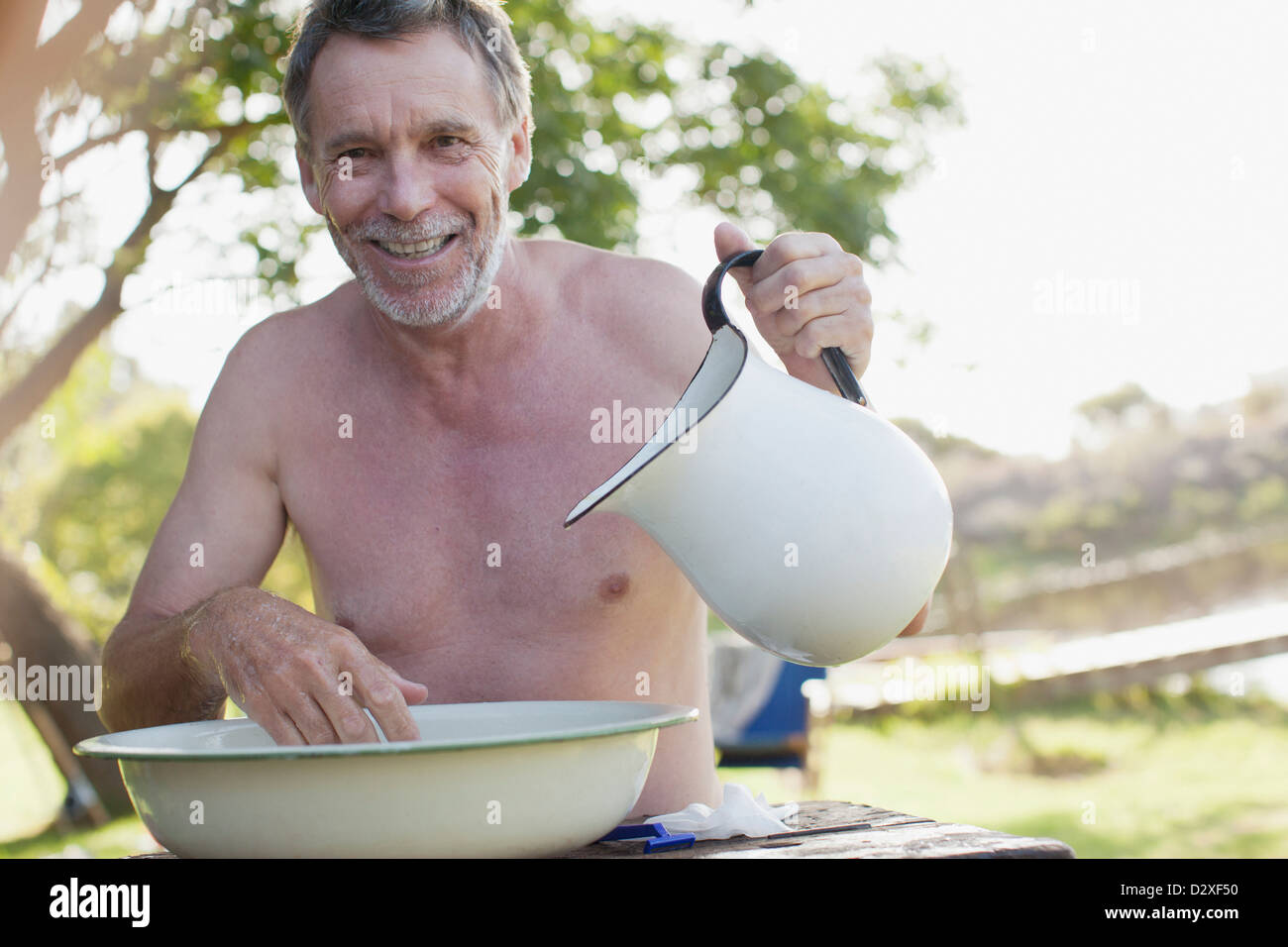 Portrait of smiling man with pitcher washing face in basin at lakeside - Stock Image