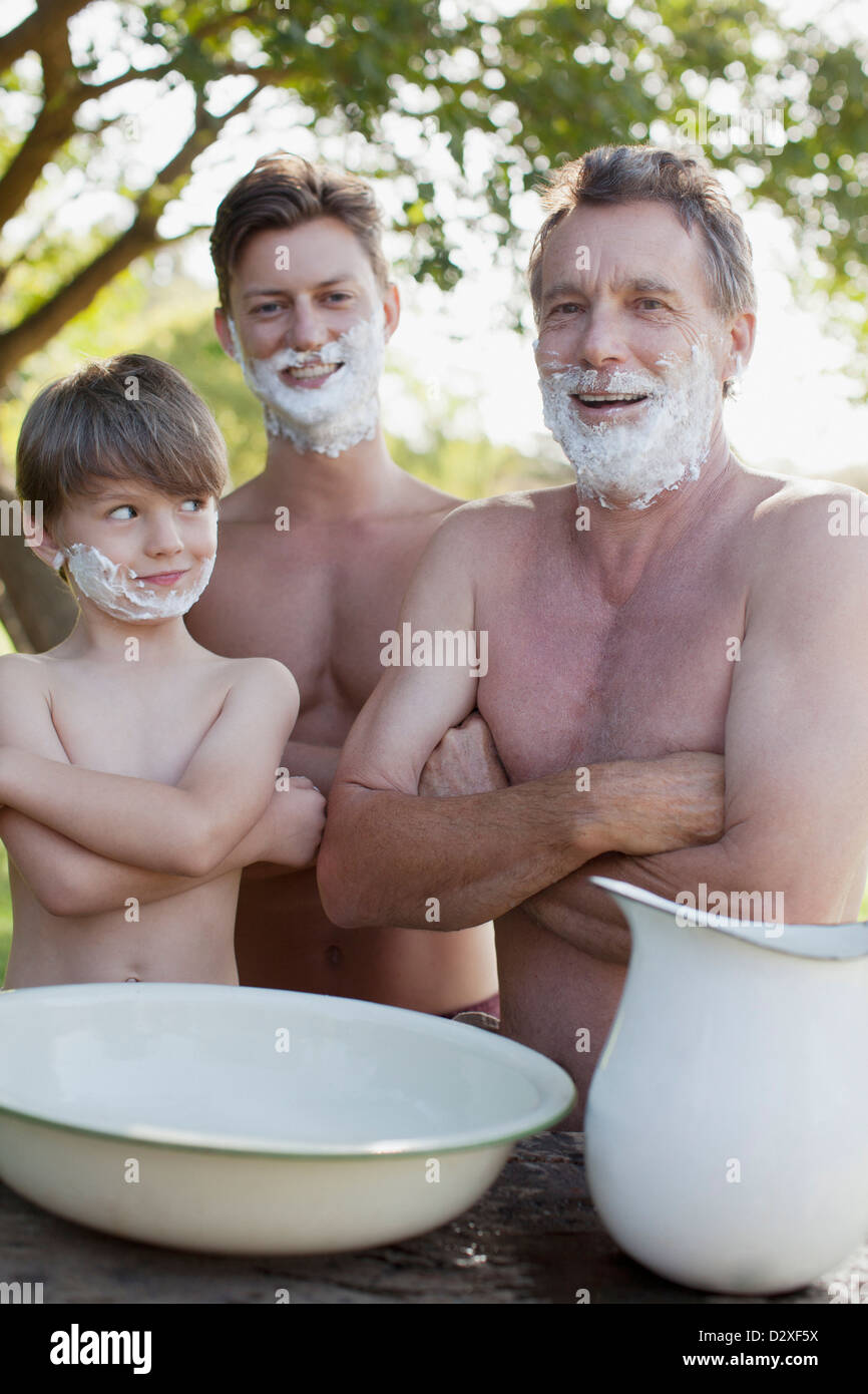 Portrait of multi-generation men with arms crossed and shaving cream on faces - Stock Image