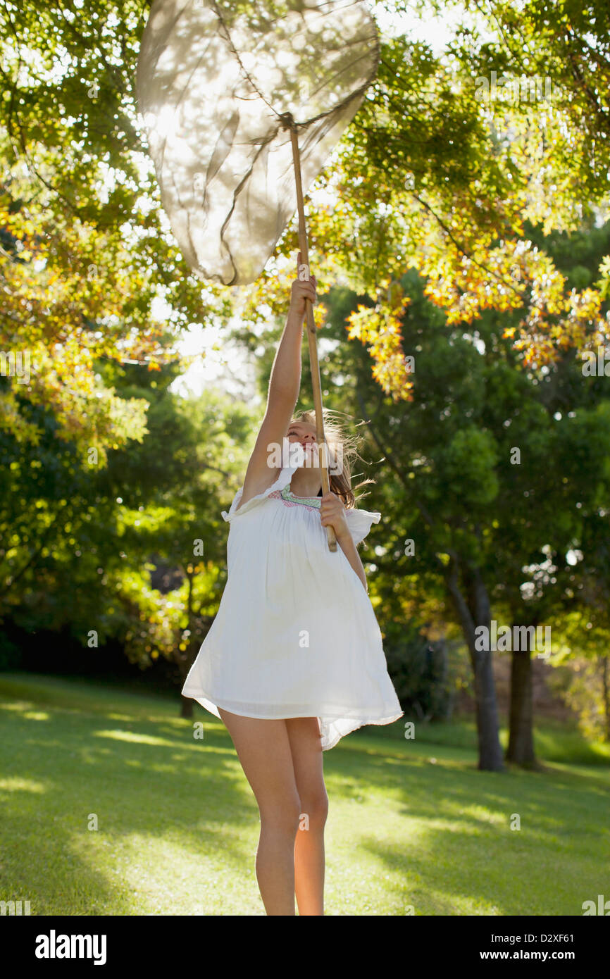 Girl in dress holding butterfly net overhead - Stock Image