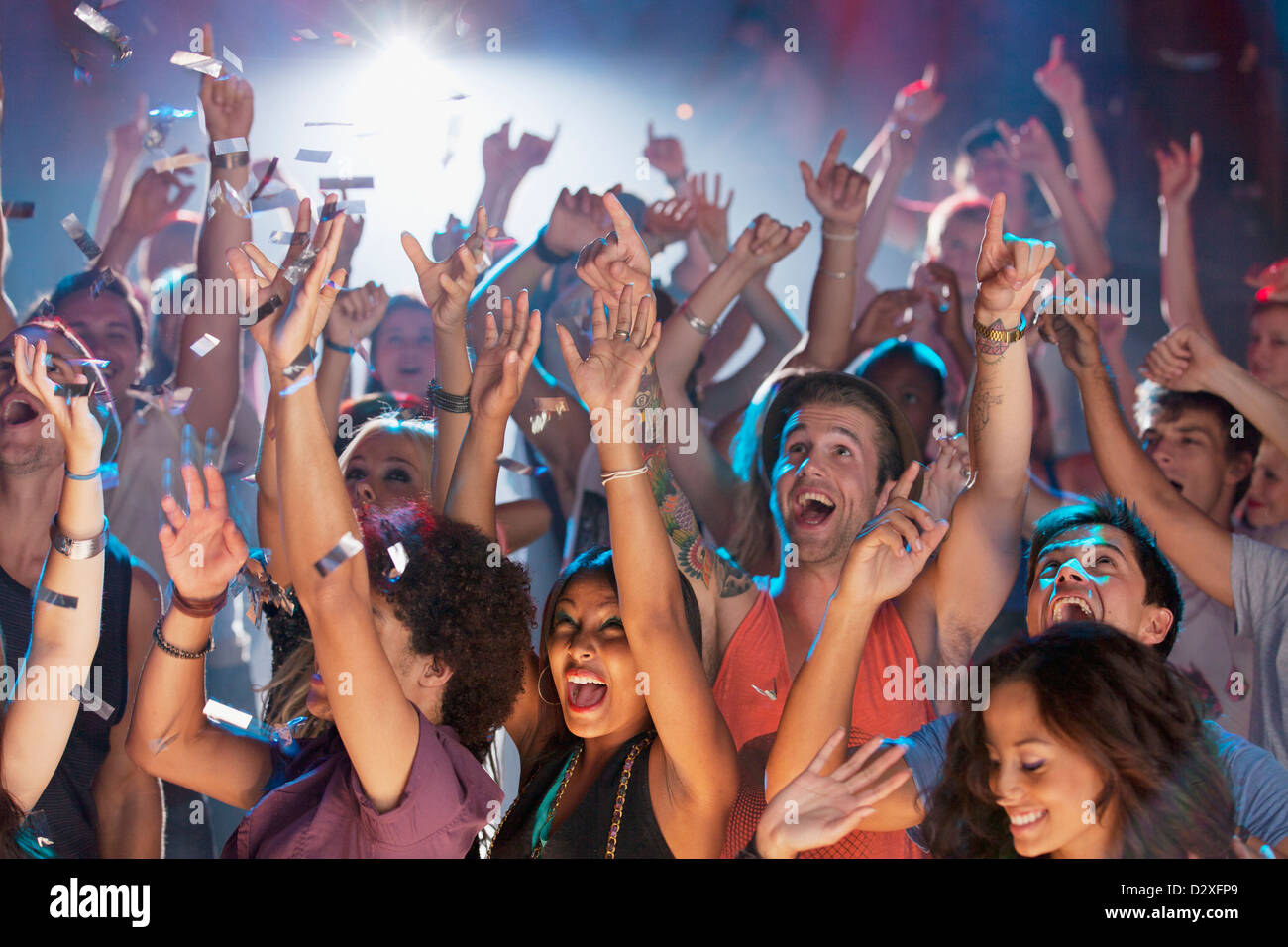 Enthusiastic crowd cheering at concert - Stock Image