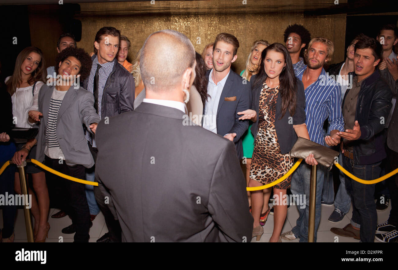 Crowd gesturing to bouncer behind rope outside night club - Stock Image