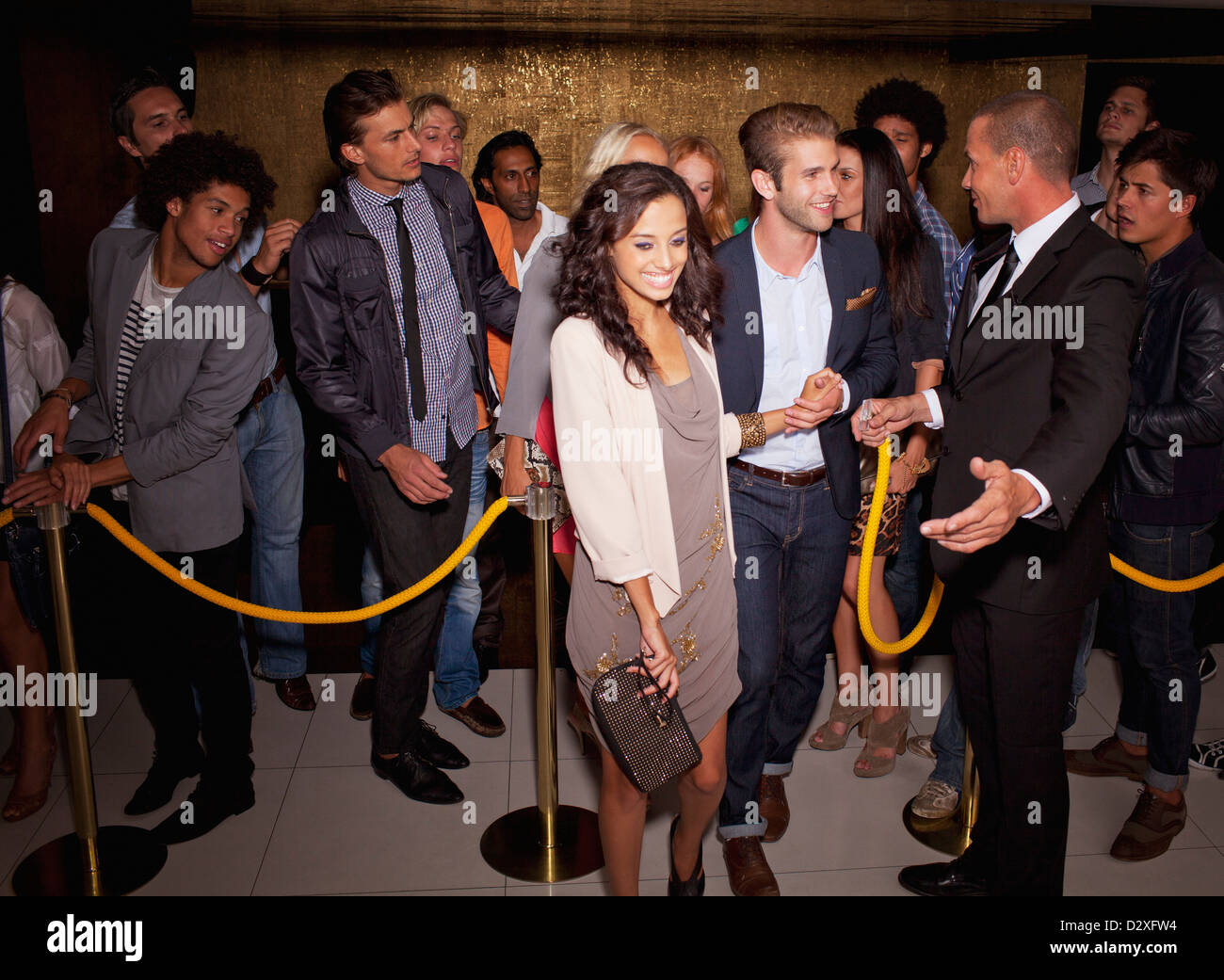 Bouncer granting couple access outside nightclub - Stock Image