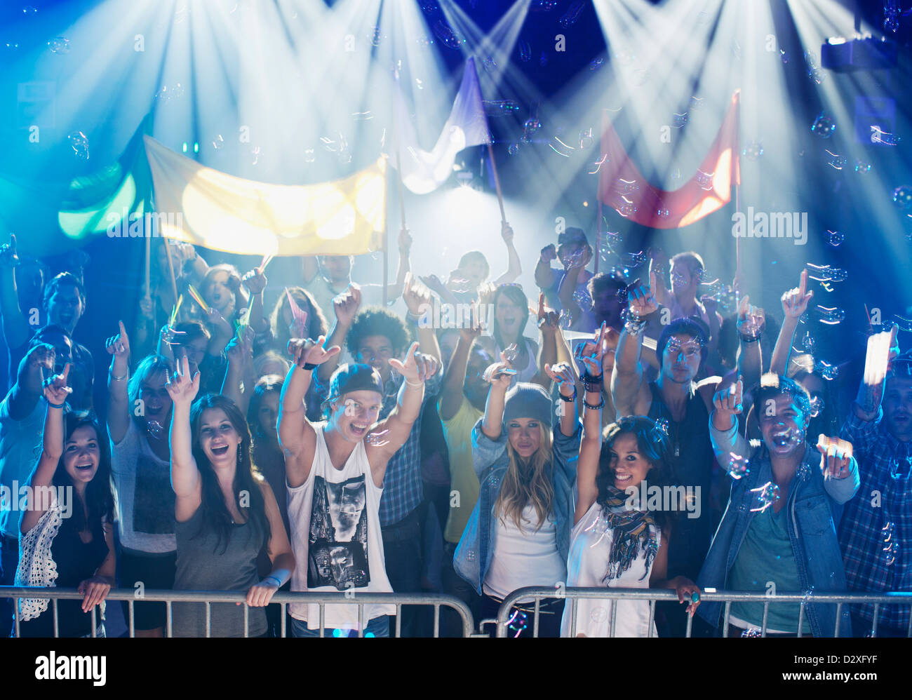 Portrait of enthusiastic crowd at concert - Stock Image