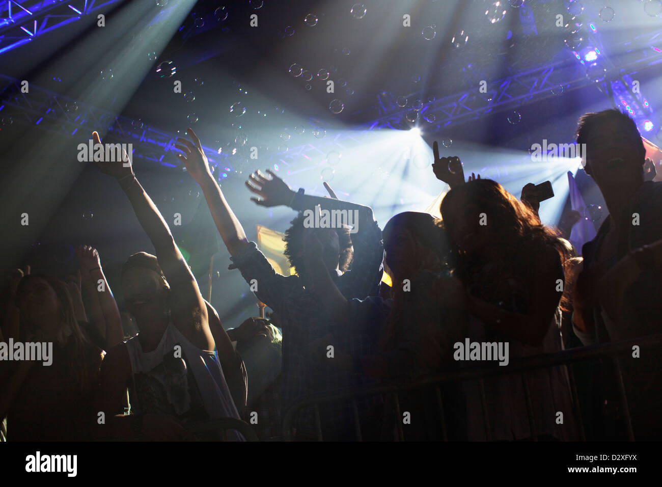 Crowd cheering with arms raised at concert - Stock Image