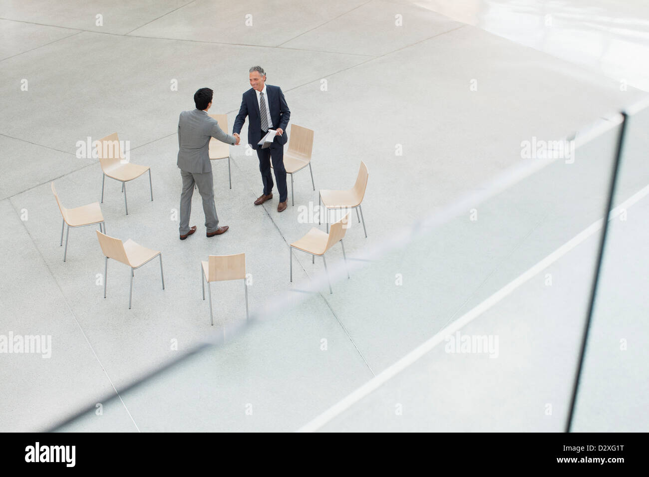 Circle of chairs around businessmen shaking hands - Stock Image