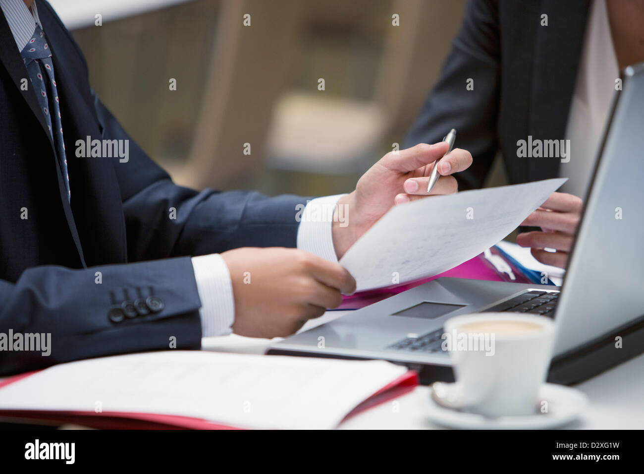 Close up of business people reviewing paperwork at cafe - Stock Image