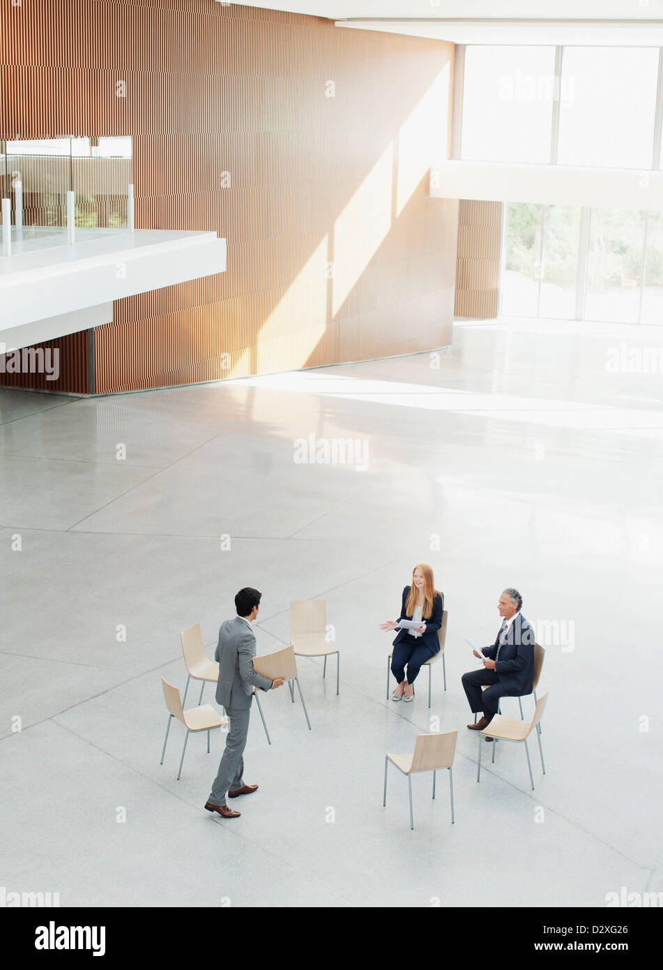 Businessman approaching co-workers at circle of chairs - Stock Image