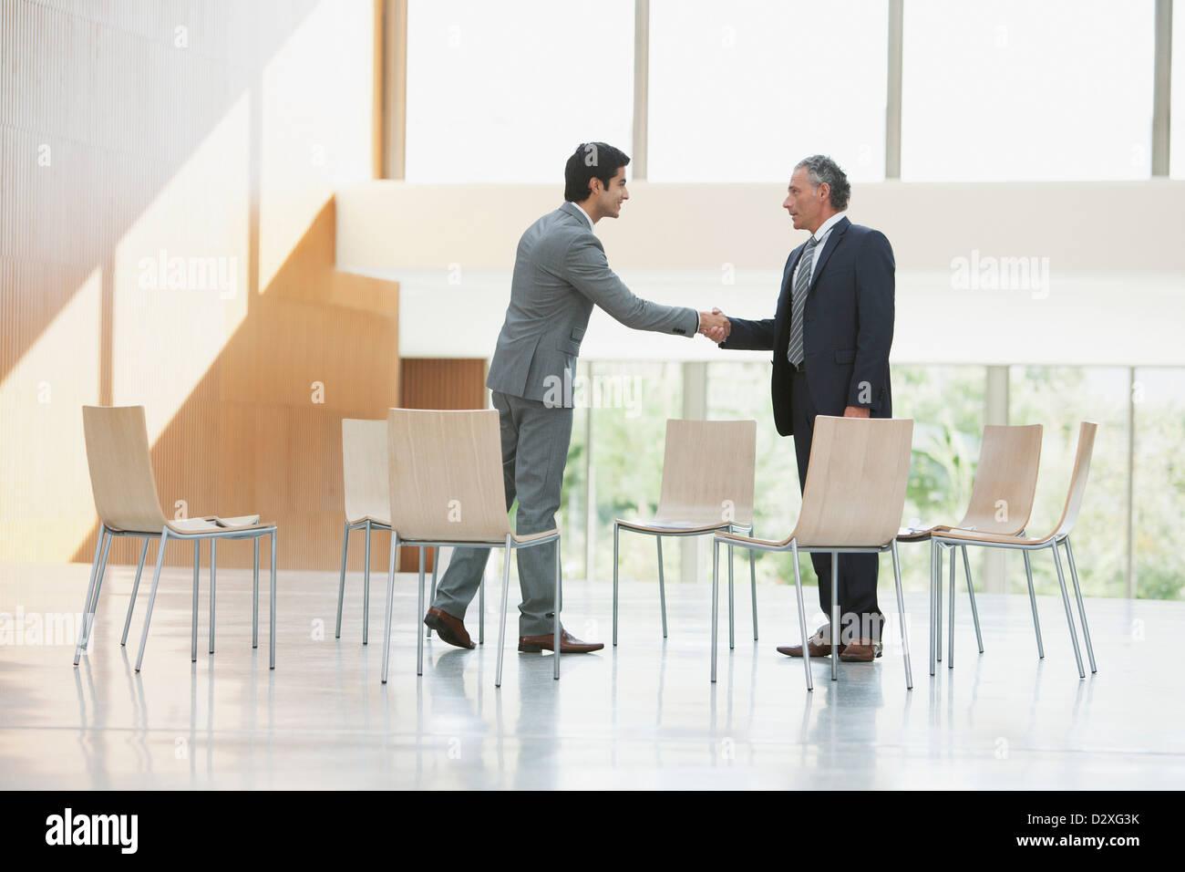 Chairs surrounding businessmen shaking hands - Stock Image