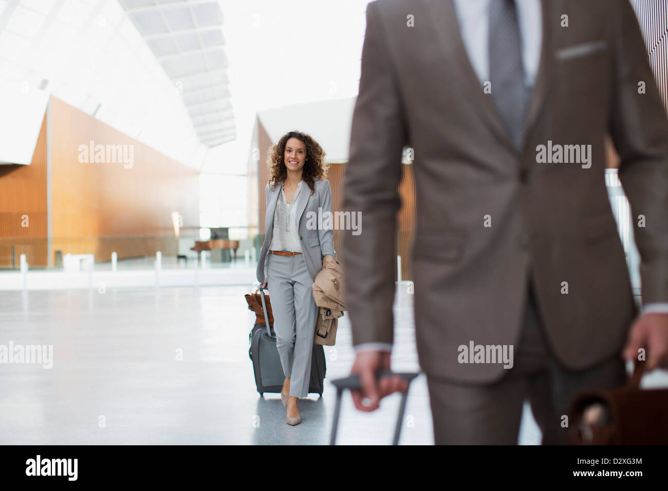 Smiling businesswoman pulling suitcase in airport - Stock Image