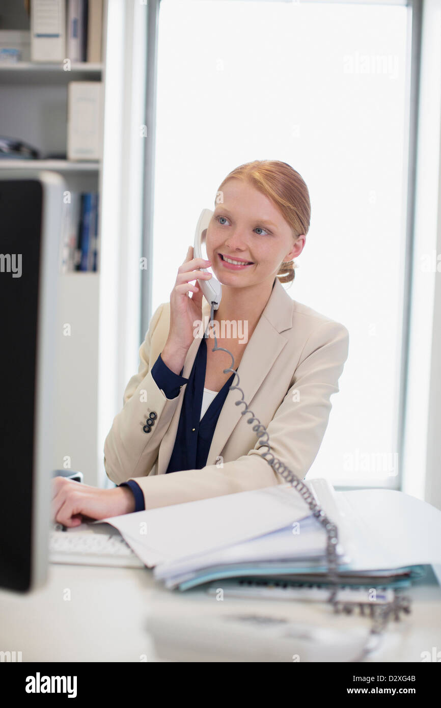 Smiling businesswoman talking on telephone - Stock Image