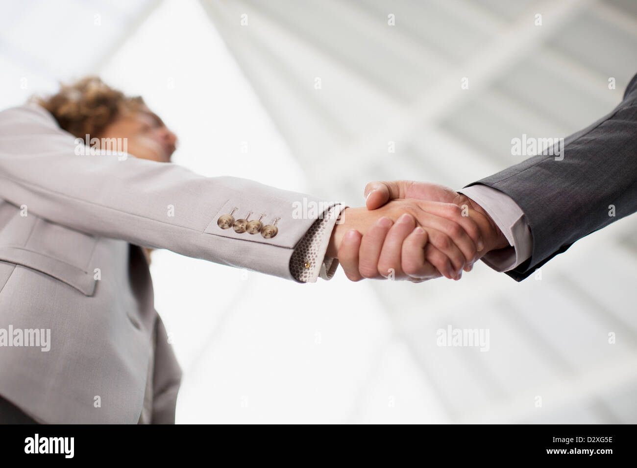 Close up of businessman and businesswoman shaking hands - Stock Image