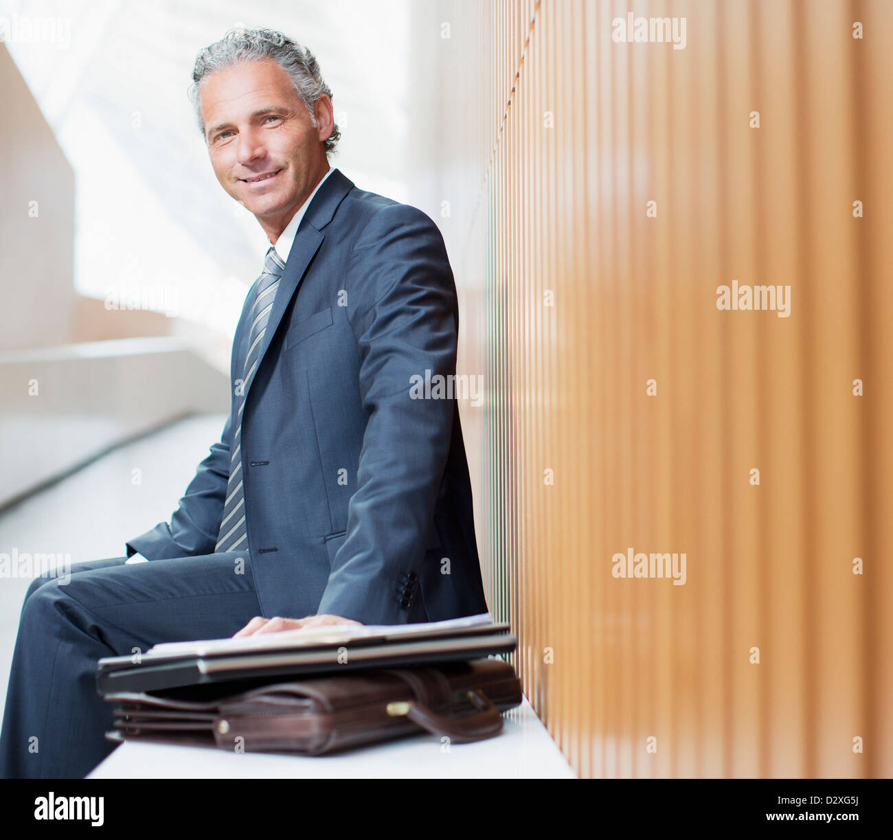 Portrait of smiling businessman with laptop and briefcase - Stock Image