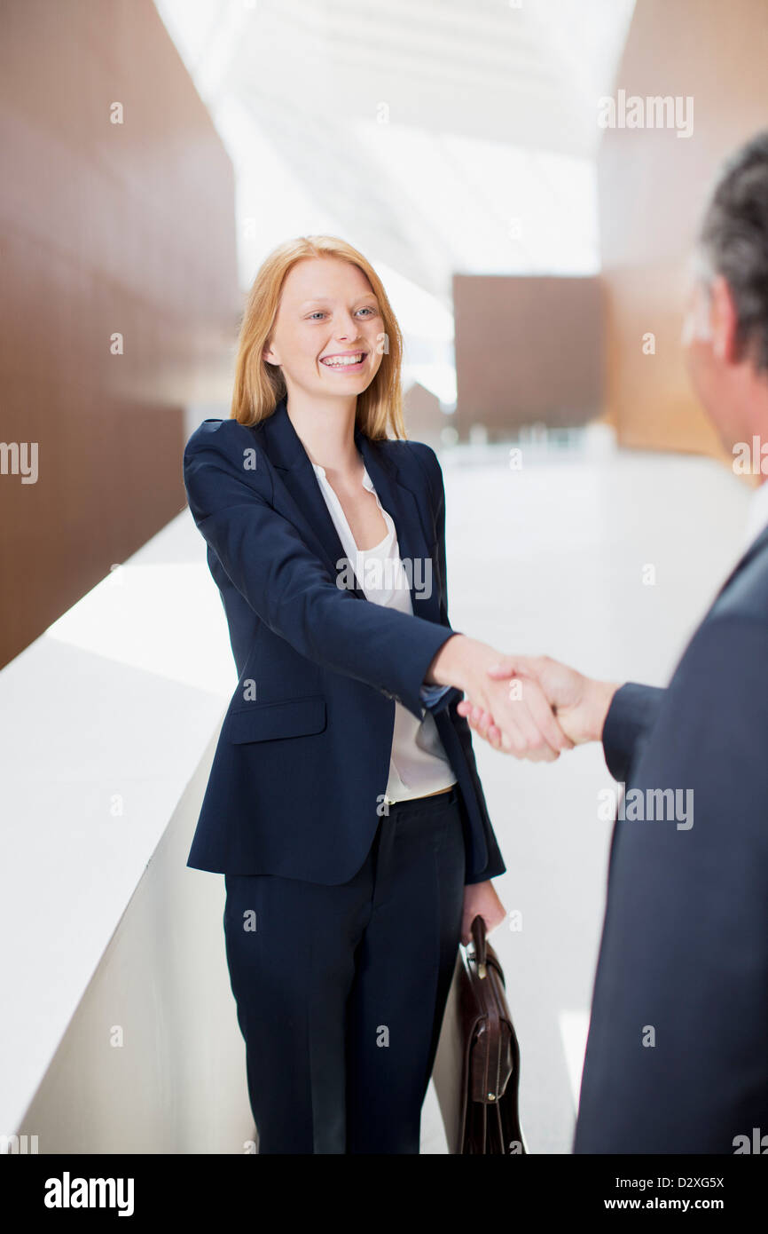 Smiling businesswoman shaking hands with businessman - Stock Image