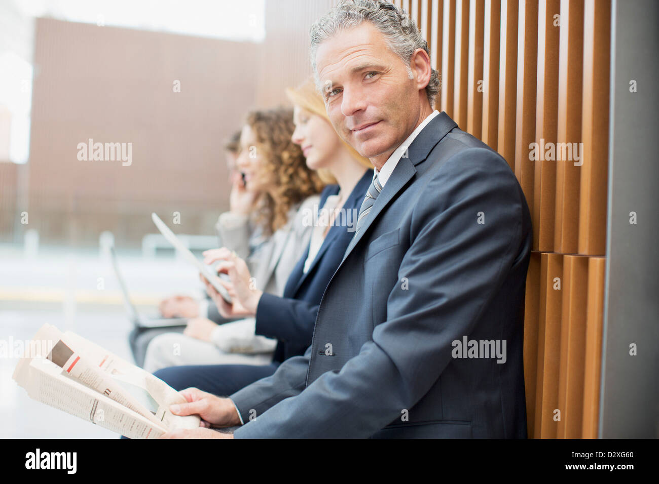 Portrait of confident businessman reading newspaper with co-workers in background - Stock Image