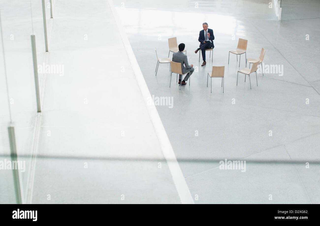 Businessmen meeting at circle of chairs in lobby - Stock Image
