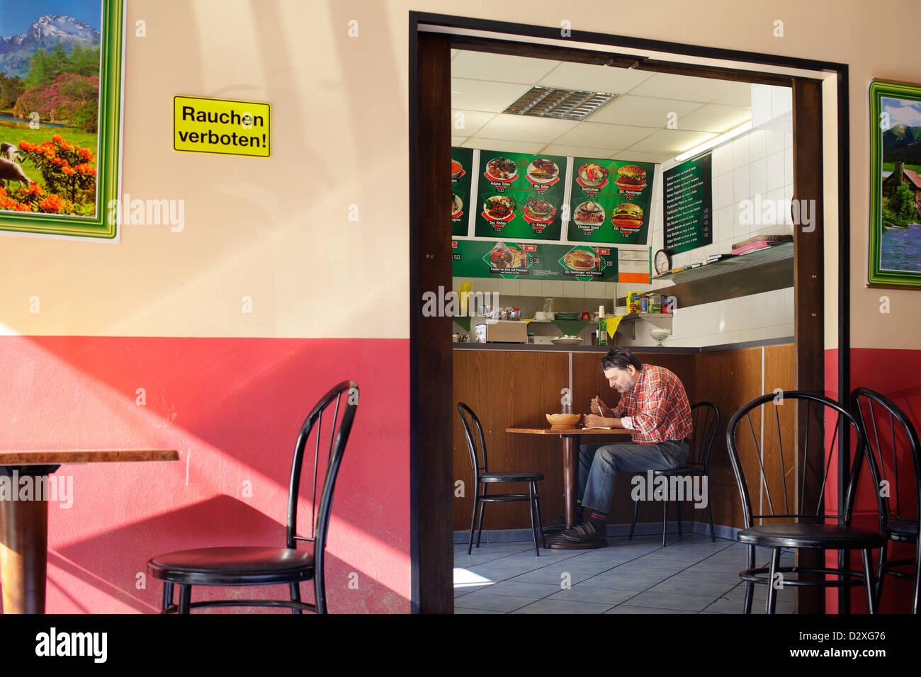 Berlin, Germany, man in a Turkish snack, hunched over his food - Stock Image
