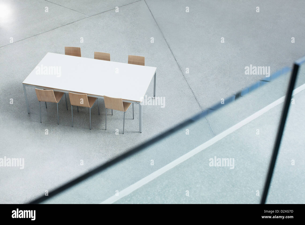Table and chairs in empty lobby - Stock Image