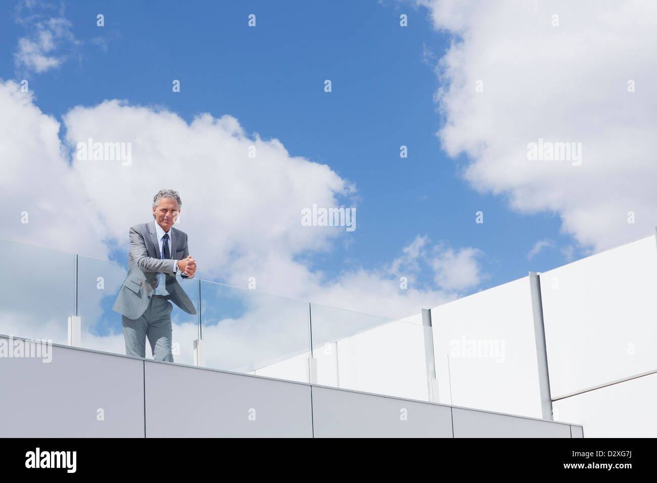 Portrait of confident businessman with hands clasped on balcony - Stock Image