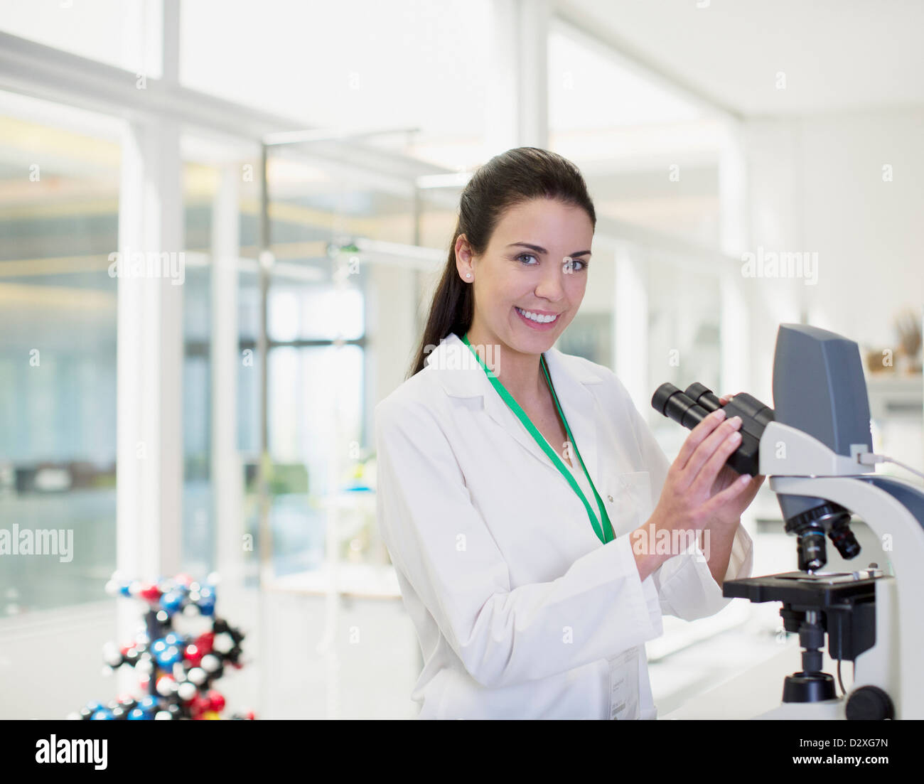 Portrait of confident scientist using microscope in laboratory - Stock Image