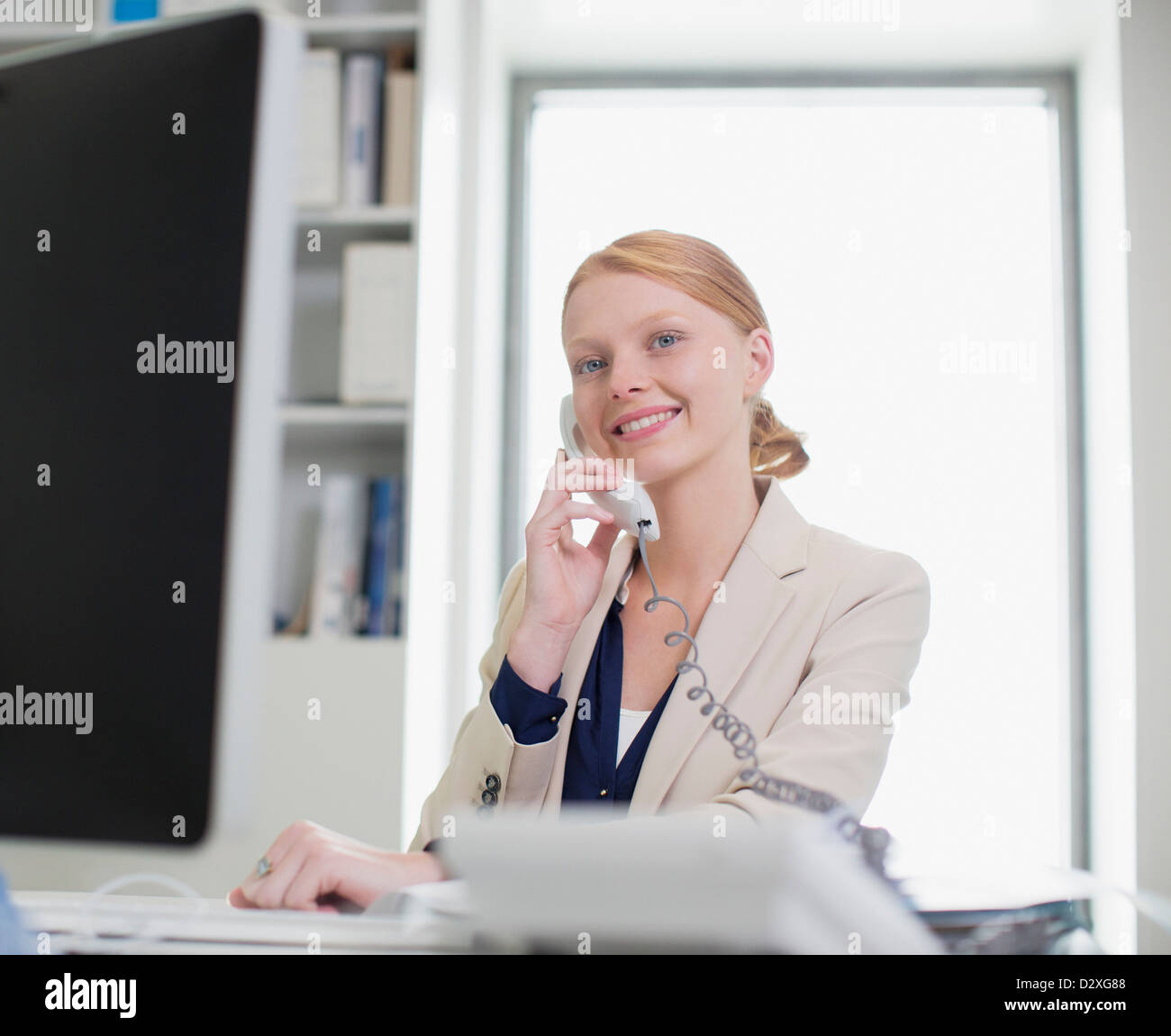 Portrait of confident businesswoman using computer and talking on telephone - Stock Image