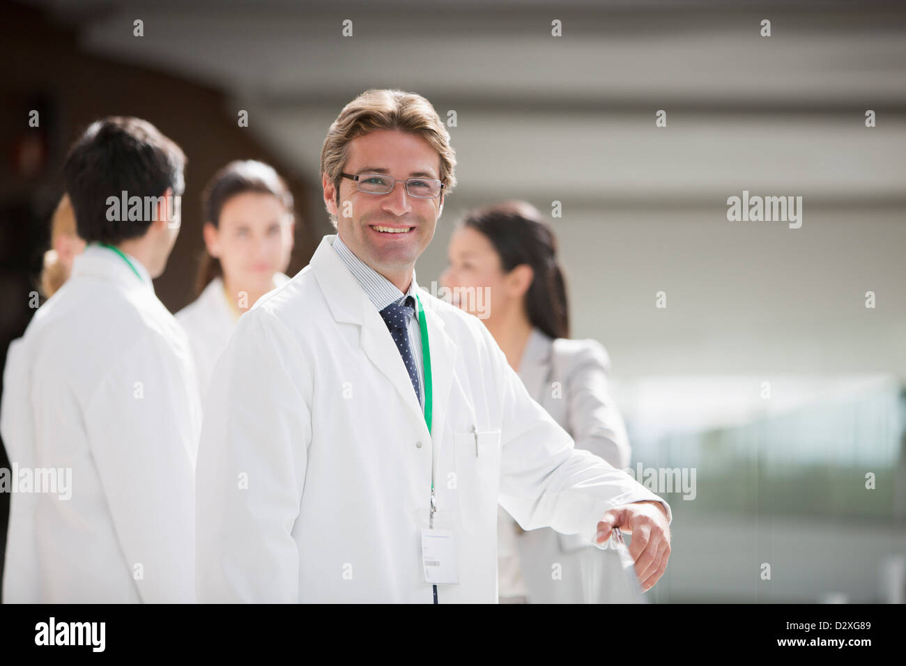 Portrait of smiling scientist with co-workers in background - Stock Image
