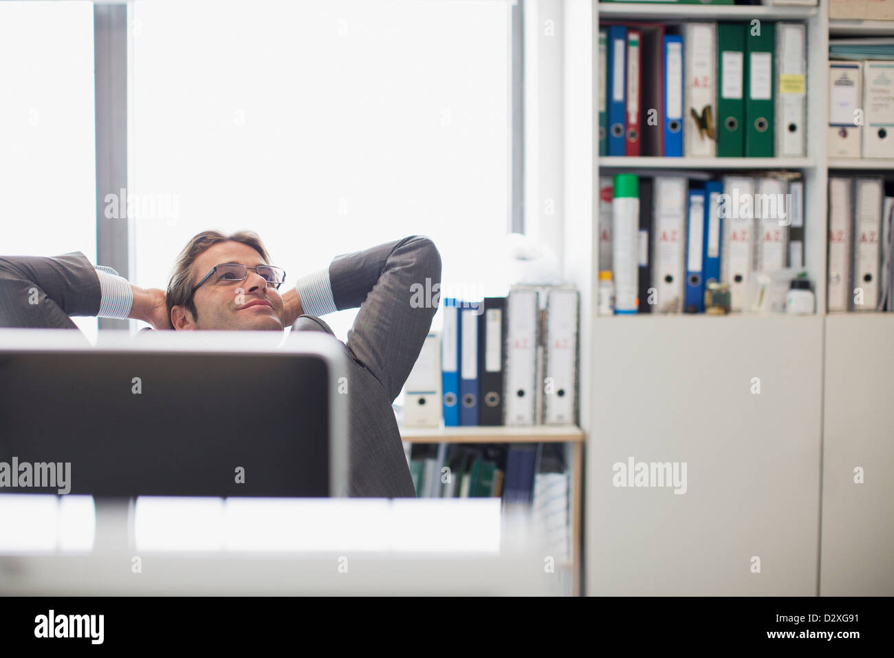 Happy businessman with head back and hands behind head in office - Stock Image