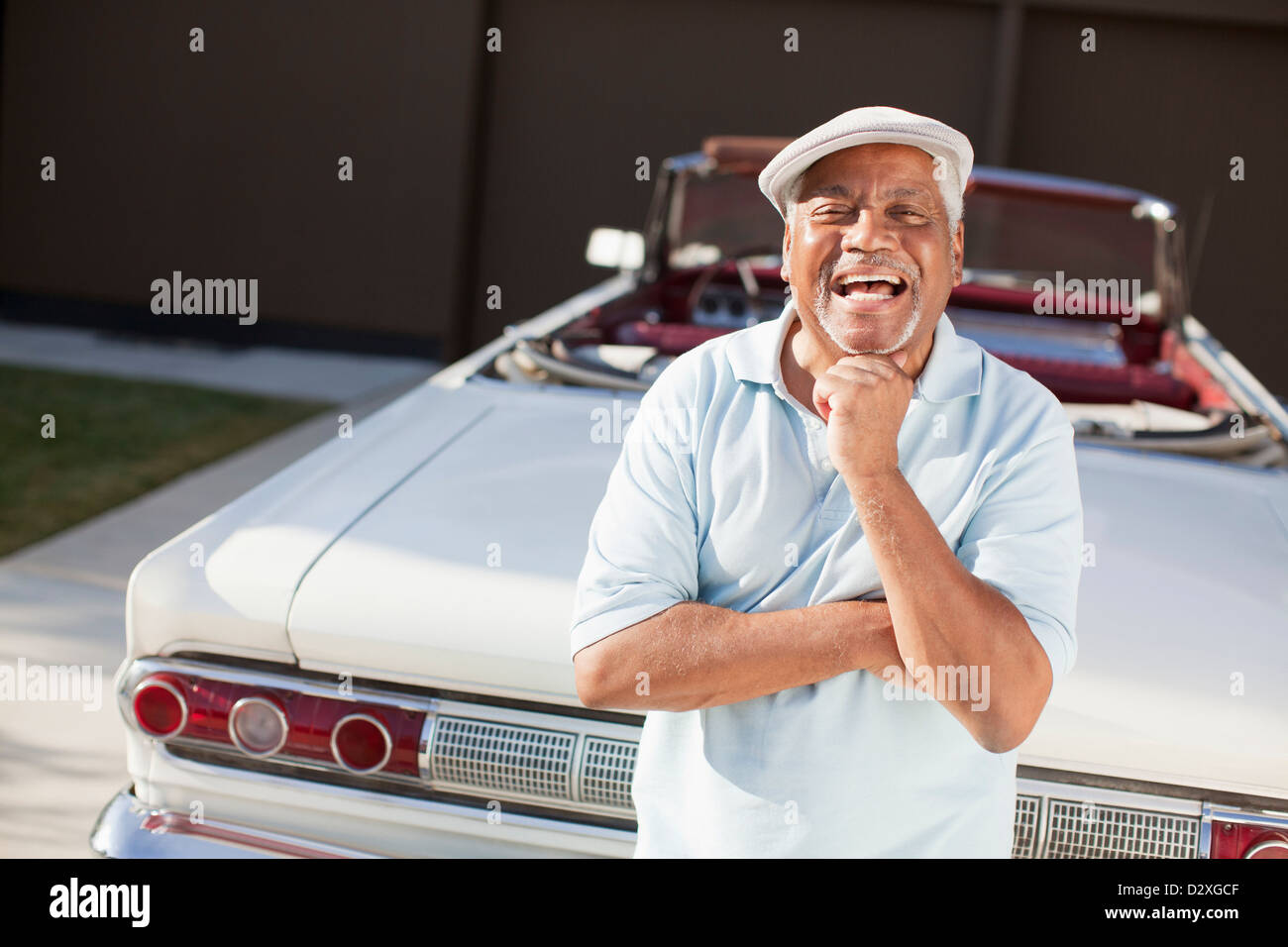 Older man smiling with convertible - Stock Image