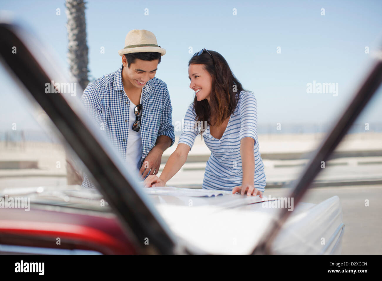 Smiling couple reading road map on convertible - Stock Image