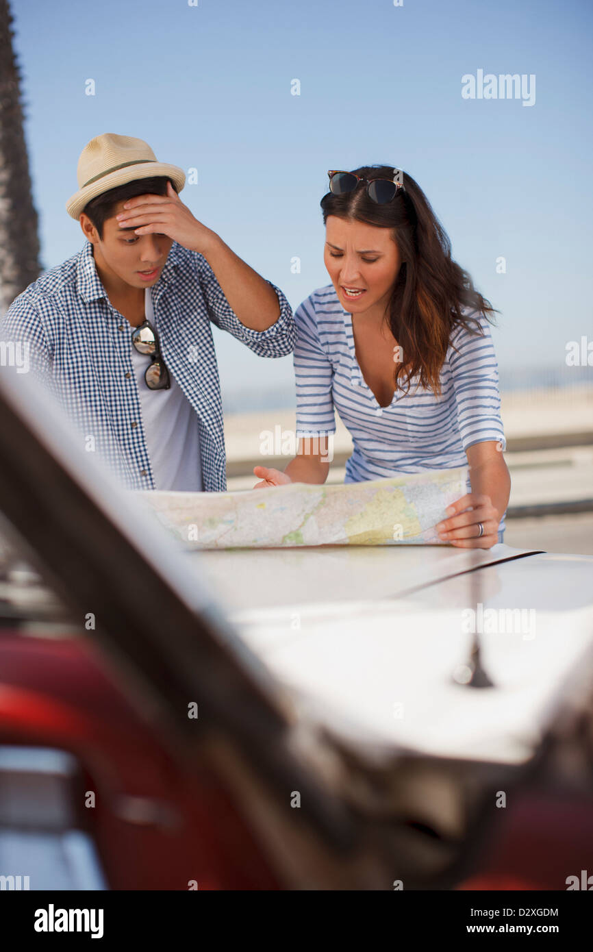 Frustrated couple reading road map - Stock Image